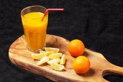 Einiges reife Zitrusfrucht und ein Glas Saft auf einem Holztisch auf einer Tafel - Mandarinen Stockfotos