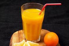 Einiges reife Zitrusfrucht und ein Glas Saft auf einem Holztisch auf einer Tafel - Mandarinen Stockbilder