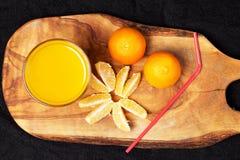 Einiges reife Zitrusfrucht und ein Glas Saft auf einem Holztisch auf einer Tafel - Mandarinen Stockfoto