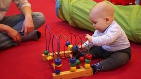 Einjährige Babyspiele, die auf dem Boden mit einem hölzernen sich entwickelnden Spielzeug sitzen Roter Hintergrund, der Vater des stock video footage
