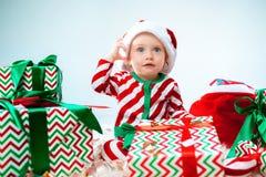 Einjähriger tragender Sankt-Hut des netten Babys, der über Weihnachtshintergrund aufwirft Sitzen auf Boden mit Weihnachtsball stockbilder