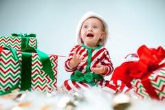 Einjähriger tragender Sankt-Hut des netten Babys, der über Weihnachtshintergrund aufwirft Sitzen auf Boden mit Weihnachtsball lizenzfreie stockfotos
