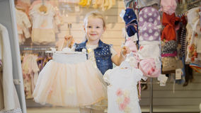 Einkauf für Kinder Das Mädchen zeigt in den Rahmenaufhängern mit Ausstattungen Lizenzfreie Stockfotografie