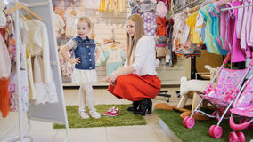 Einkauf für Kinder Mutter und Tochter bewundern ihre Kleidung vor dem Spiegel Lizenzfreie Stockfotografie