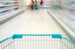 Einkauf im Supermarkt durch Supermarktwarenkorb lizenzfreies stockbild