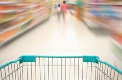 Einkauf im Supermarkt durch Supermarktwarenkorb stockfoto