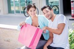 Einkauf mit Ihrem geliebten Paare, die auf einer Bank und einem Griff sitzen Stockbild