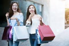 Einkauf mit zwei junger glücklicher asiatischer Frauen im Freien stockfotos