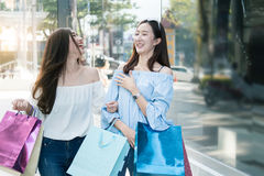 Einkauf mit zwei junger glücklicher asiatischer Frauen im Freien Stockfotografie