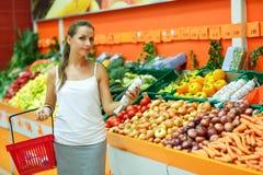 Einkaufen der jungen Frau in einem Supermarkt in der Abteilung der Frucht Lizenzfreies Stockbild