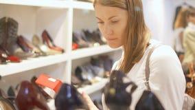 Einkaufen der jungen Frau für Schuhe im Mall Wählen von Stiletten Ansicht durch Schaufenster Reihen von Schuhen stock video footage