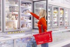 Einkaufen der jungen Frau am Supermarkt lizenzfreie stockfotos