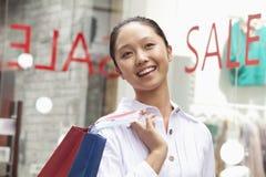 Einkaufen der jungen Frau vor Verkaufszeichen Lizenzfreie Stockfotos