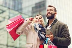 Einkaufen des glücklichen Paars in der Stadt stockfotografie