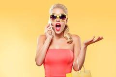 Einkaufen Die junge lächelnde Frau, die Tasche halten und das Gespräch durch Handy stellen ihren Daumen oben in schwarzem Freitag Lizenzfreies Stockfoto
