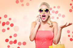 Einkaufen Die junge lächelnde Frau, die Tasche halten und das Gespräch durch Handy stellen ihren Daumen oben in schwarzem Freitag Stockbild
