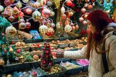 Einkaufen für Weihnachtsfeiertage, junge Frau am Marktanzeigenfenster, das Baumdekorationen wählt stockfotos