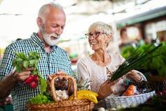 Einkaufen, Lebensmittel, Verkauf, Verbraucherschutzbewegung und Leutekonzept - gl?ckliches ?lteres Paar, das neues Lebensmittel k lizenzfreie stockfotos