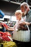 Einkaufen, Lebensmittel, Verkauf, Verbraucherschutzbewegung und Leutekonzept - gl?ckliches ?lteres Paar, das neues Lebensmittel k stockbild