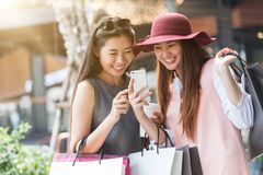 Einkaufen mit zwei Frauen zusammen mit Einkaufstaschen in der Hand und der Anwendung Stockfotografie