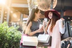 Einkaufen mit zwei Frauen zusammen mit Einkaufstaschen in der Hand und der Anwendung Lizenzfreie Stockfotografie