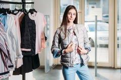 Einkaufen, Mode, Art, Verkauf, Einkaufen, Geschäft und Leute schöne glückliche junge Frau des Konzeptes im Bekleidungsgeschäft Ge lizenzfreies stockbild