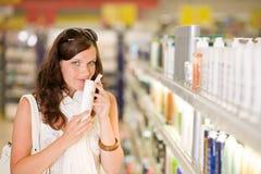 Einkaufenkosmetik - riechendes Shampoo der Frau Lizenzfreie Stockfotografie