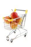 Einkaufenlaufkatze und -äpfel Stockfotos
