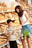 Einkaufenserie - Mutter mit kaufendem Brot des Kindes Lizenzfreie Stockfotografie