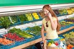 Einkaufenserie - rote Haarfrau in einem Supermarkt Lizenzfreies Stockbild