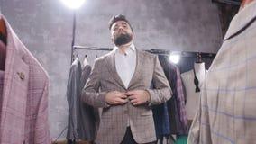Einkaufs- und Modekonzept - wählende und versuchende Jacke des jungen bärtigen Mannes an im Mall oder im Bekleidungsgeschäft stock video footage