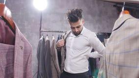 Einkaufs- und Modekonzept - wählende und versuchende Jacke des jungen bärtigen Mannes an im Mall oder im Bekleidungsgeschäft stock footage