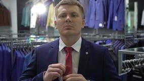 Einkaufs- und Modekonzept - wählende und versuchende Jacke des jungen Mannes an im Mall oder im Bekleidungsgeschäft stock video footage
