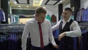 Einkaufs- und Modekonzept - wählende und versuchende Jacke des jungen Mannes an im Mall oder im Bekleidungsgeschäft stock footage
