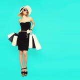 Einkaufsferienart Bezaubernde Dame, die Taschen auf blauem BAC hält stockfoto