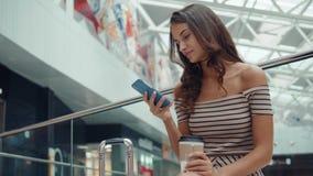 Einkaufsfrau, die mit den Taschen sprechen am Telefon im Mall lächelt Schönes Mädchen mit Smartphone im Einkaufszentrengepäck stock video footage