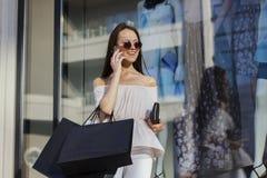 Einkaufsfrau, die am Telefon spricht lizenzfreie stockfotos