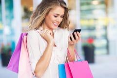 Einkaufsfrauenversenden von sms-nachrichten stockfoto