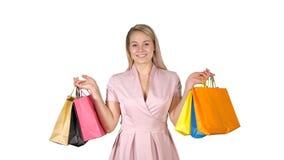 Einkaufsglückliches lächelndes haltenes iwhile Gehen der Einkaufstaschen der frau auf weißen Hintergrund stockfotos