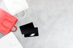 Einkaufshintergrund: rote und weiße Papiertüten und Kreditkarten Stockbild