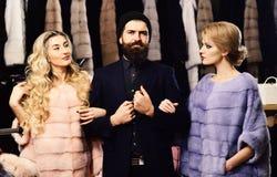 Einkaufskonzept der Damen Frauen in den violetten und rosa Pelzmänteln lizenzfreie stockfotografie