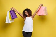 Einkaufskonzept - nahes hohes Porträt-junge schöne attraktive Afrikanerin lächelnd und froh mit dem bunten Einkaufen stockfotos