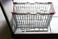 Einkaufskorb auf dem Laptop, der abstraktes Hintergrundon-line-konzept kauft Lizenzfreies Stockbild