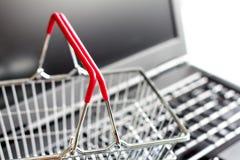 Einkaufskorb auf dem Laptop, der abstraktes Hintergrundon-line-konzept kauft Stockfotos