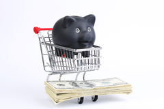 Einkaufskorb mit schwarzem Sparschwein und Stapel des Geldamerikaners hundert Dollarscheine auf weißem Hintergrund Lizenzfreie Stockfotos