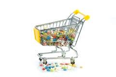 Einkaufslaufkatze mit den Pillen lokalisiert auf weißem Hintergrund Stockfotos