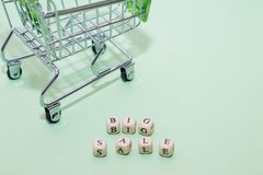 Einkaufslaufkatze und großer Verkauf des Wortes von den Würfeln auf einem grünen backgro Stockbild