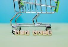 Einkaufslaufkatze und großer Verkauf des Wortes von den Würfeln auf einem grünen backgro Stockfotografie