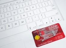 Einkaufslaufkatze und -Kreditkarte auf der Tastatur Lizenzfreie Stockfotografie