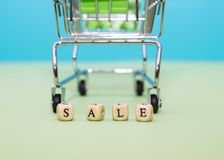 Einkaufslaufkatze und Wortverkauf von den Würfeln auf einem grünen Hintergrund Stockbilder